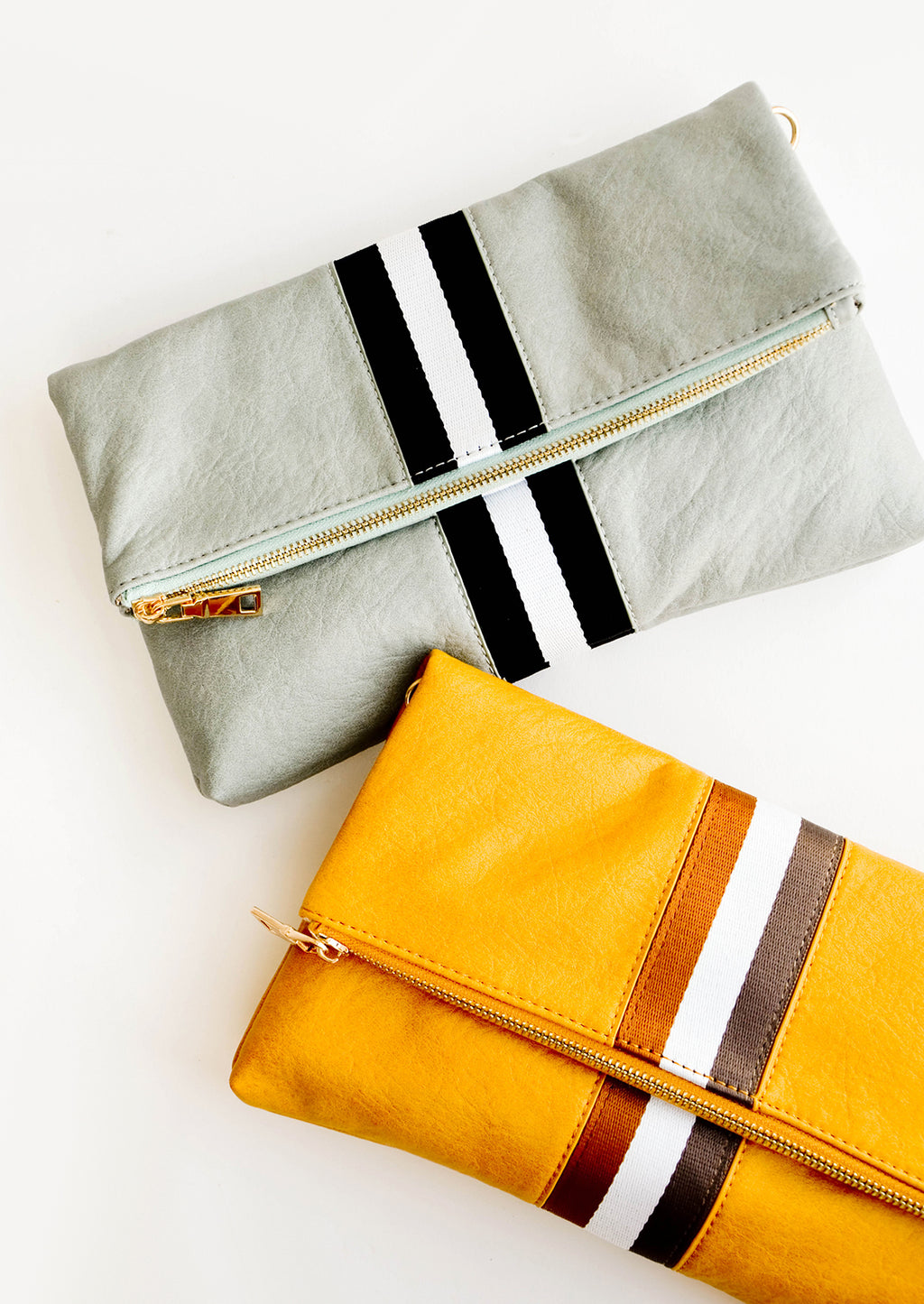 1: One mint green fold over clutch with a trio of black and white vertical stripes and one mustard yellow fold over clutch with a trio of white and brown vertical stripes.