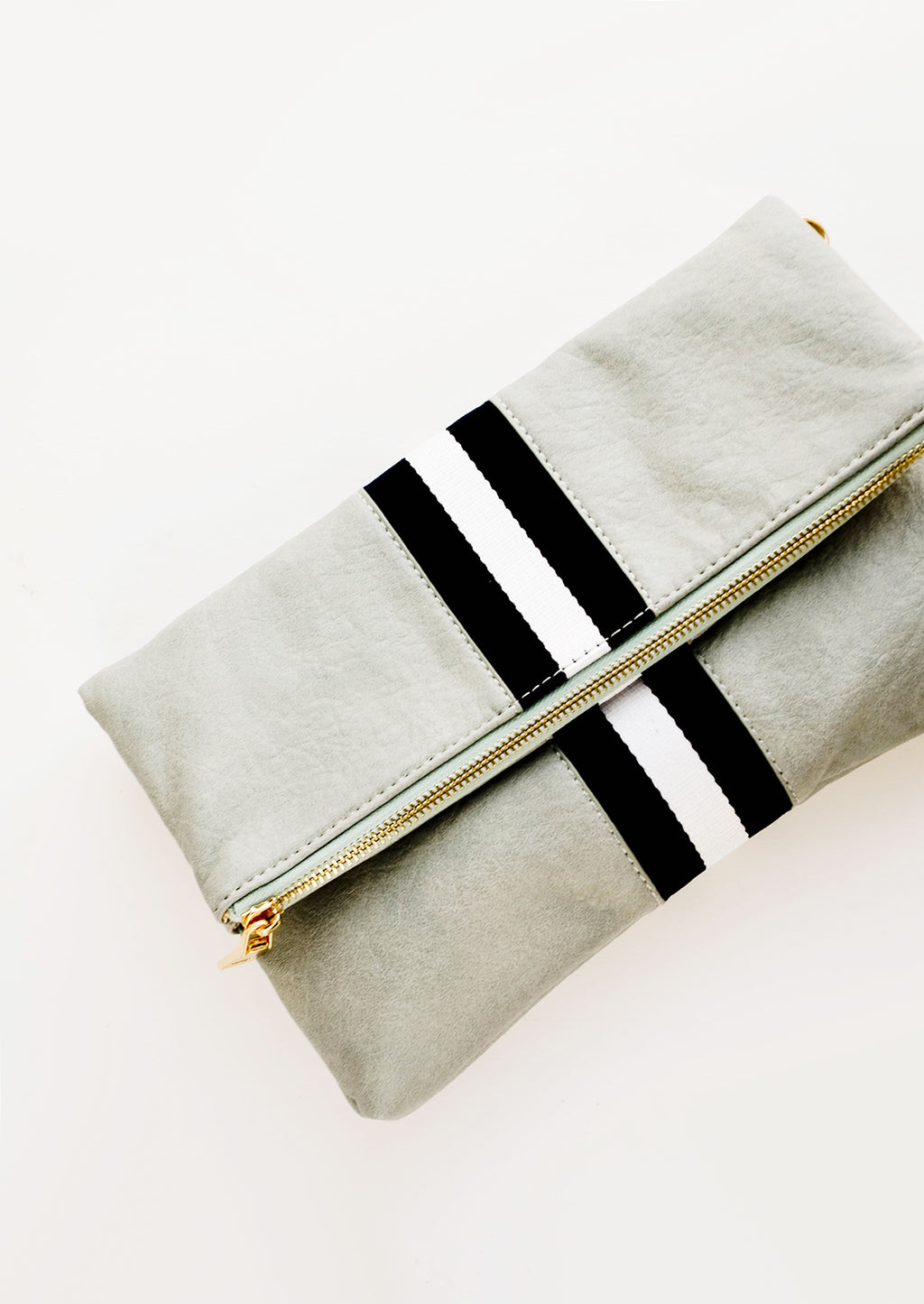 Mint / Black: A mint green fold over clutch with a trio of black and white vertical stripes.