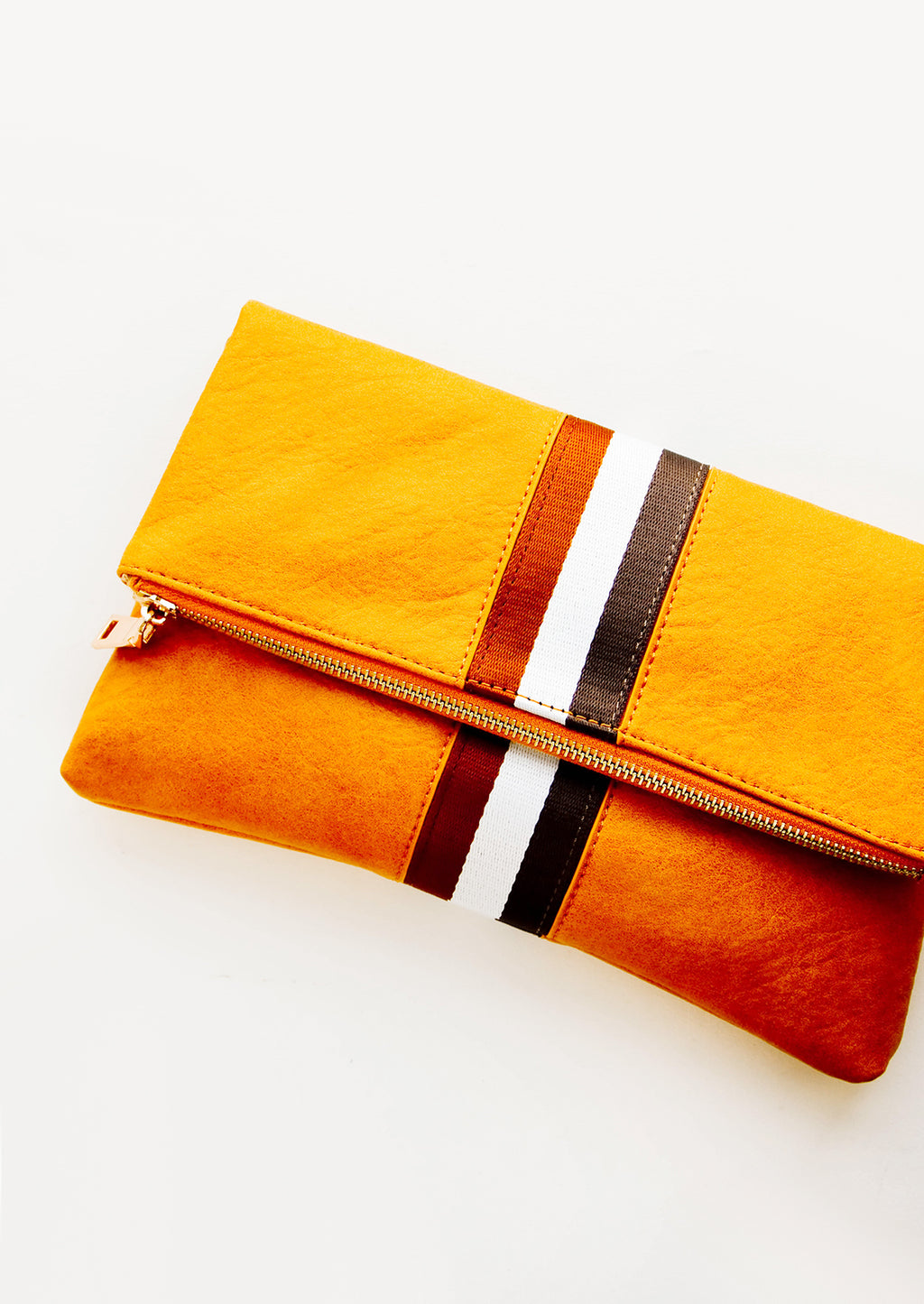 Mustard / Tan: A mustard yellow fold over clutch with a trio of white and brown vertical stripes.