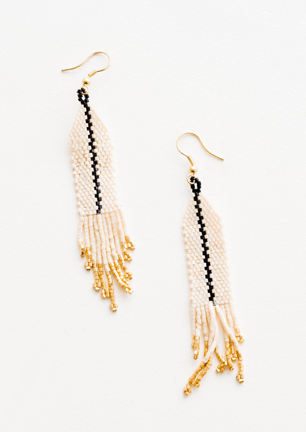 Ivory: Dangling beaded earrings with white beads accented with black bead stripe and gold bead fringe.