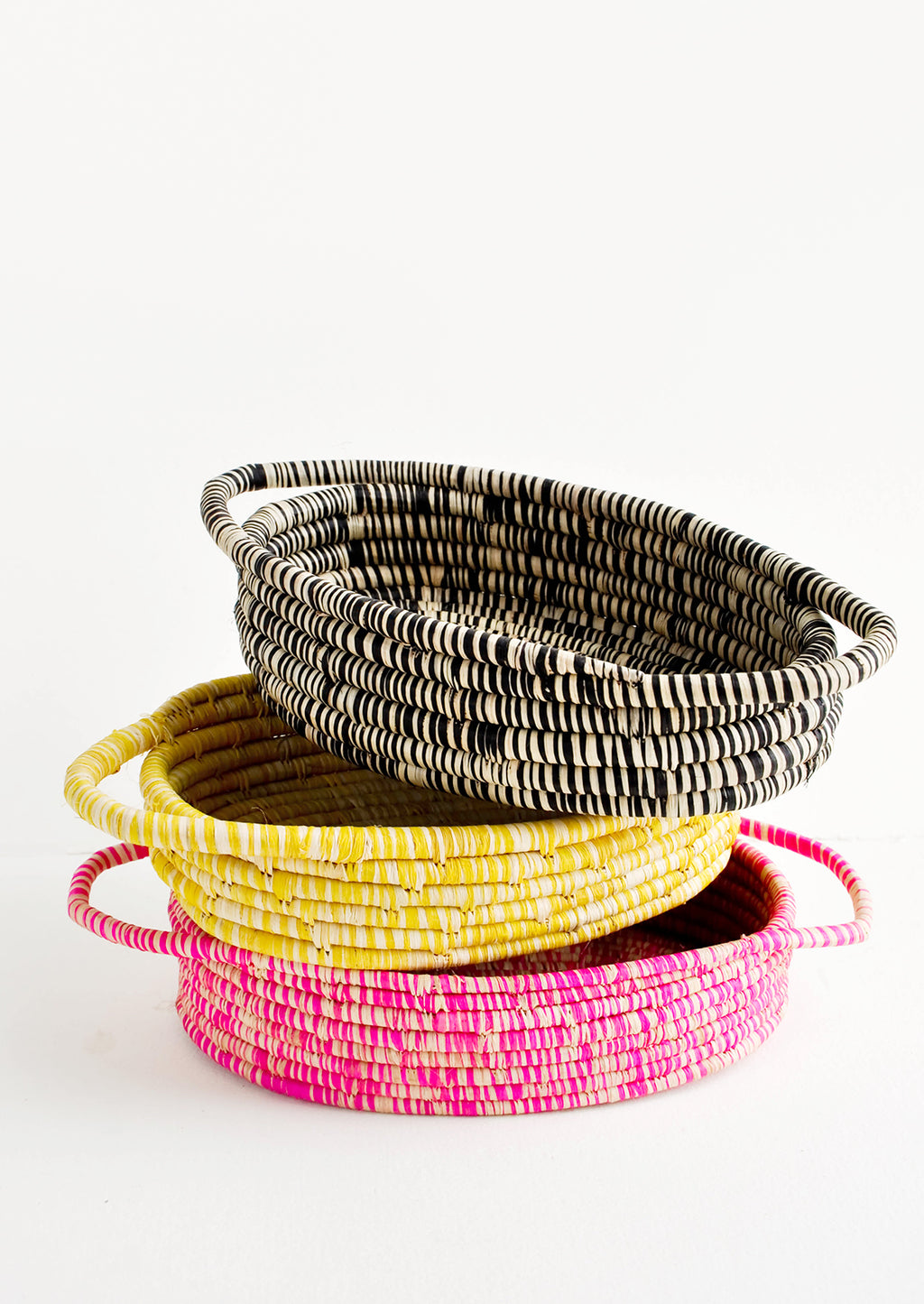 Black: Stack Of Oval Shaped Raffia Baskets in black, yellow, and pink.
