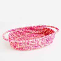 Pink: Oval Shaped, Shallow Raffia Basket with two handles at either end in Pink