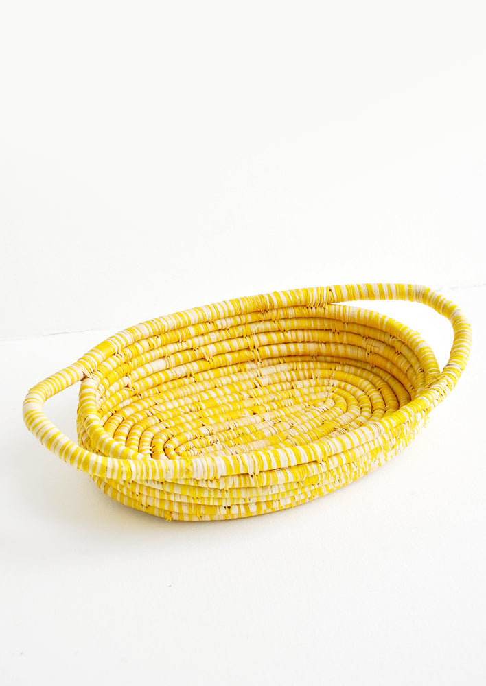 Yellow: Oval Shaped, Shallow Woven Raffia Basket with two side handles in yellow.