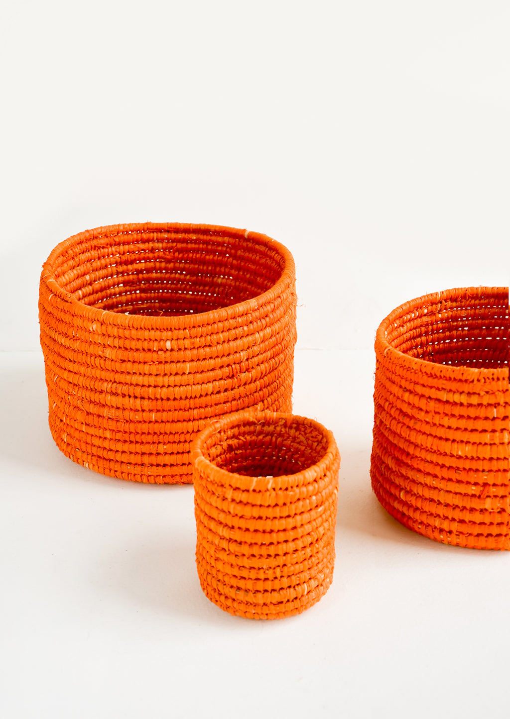 Extra Small / Orange: Set of round catchall baskets made from orange raffia in three incremental sizes.