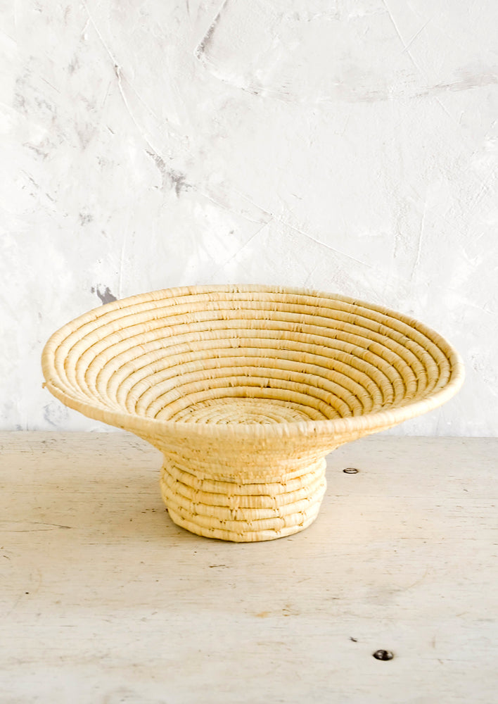 3: Footed pedestal bowl made from natural woven raffia, sitting on a table