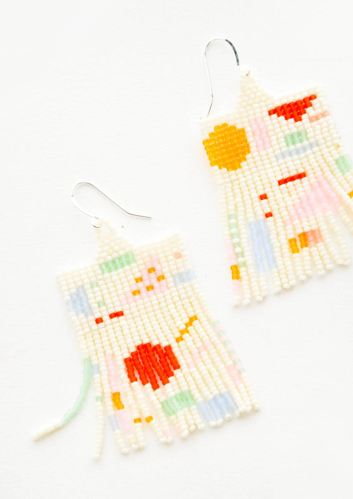 1: Cream colored glass bead fringe earrings with pattern of colorful geometric shapes on silver ear wire.