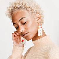 2: Model wears fringe earrings of cream and multicolored beads.
