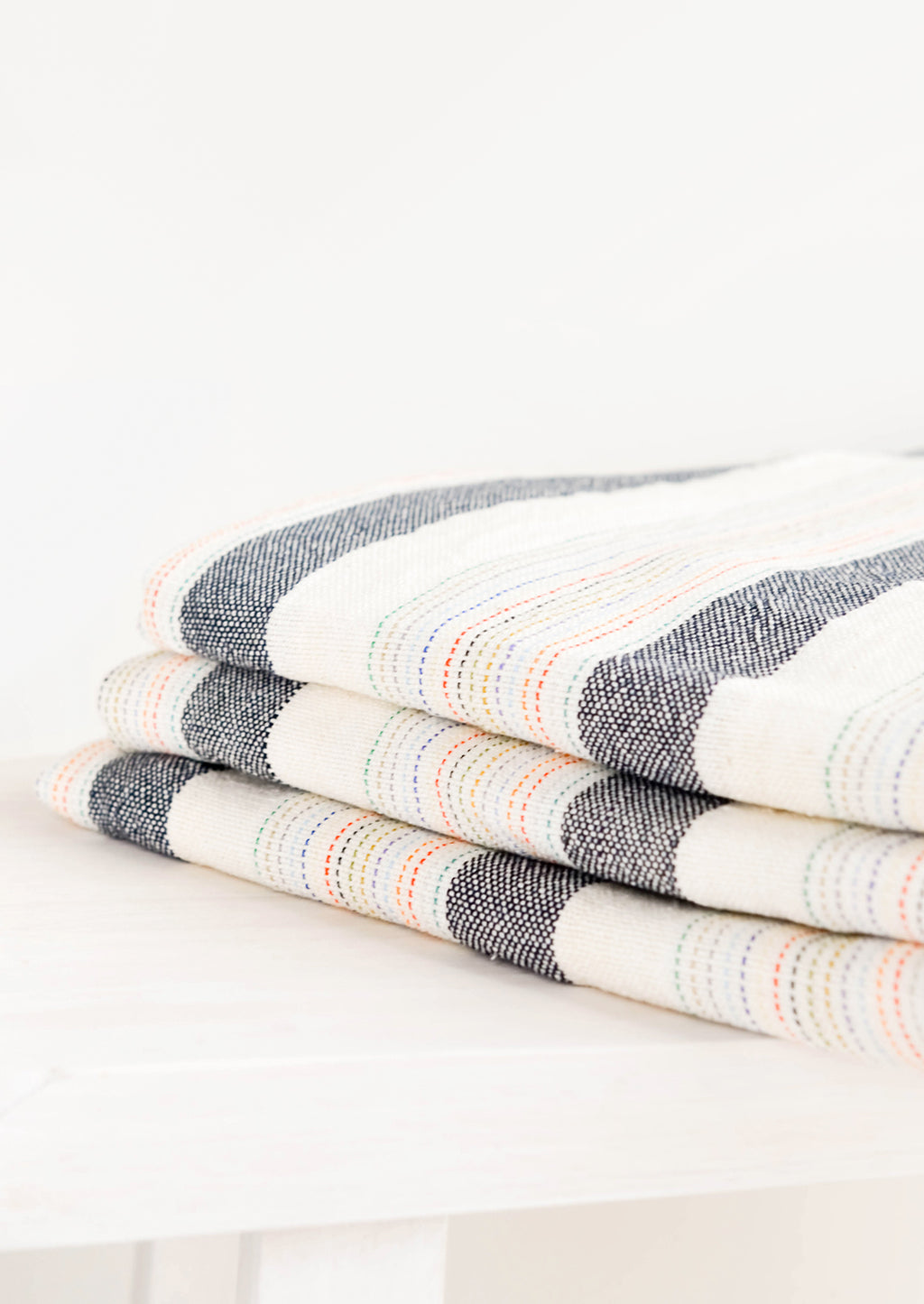 2: Stack of Cotton Turkish Towel in Natural & Charcoal with Rainbow Colored Stitching - LEIF