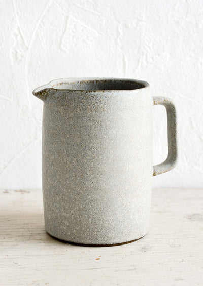 A ceramic pitcher in rustic blue-grey glaze and modern, minimal silhouette.
