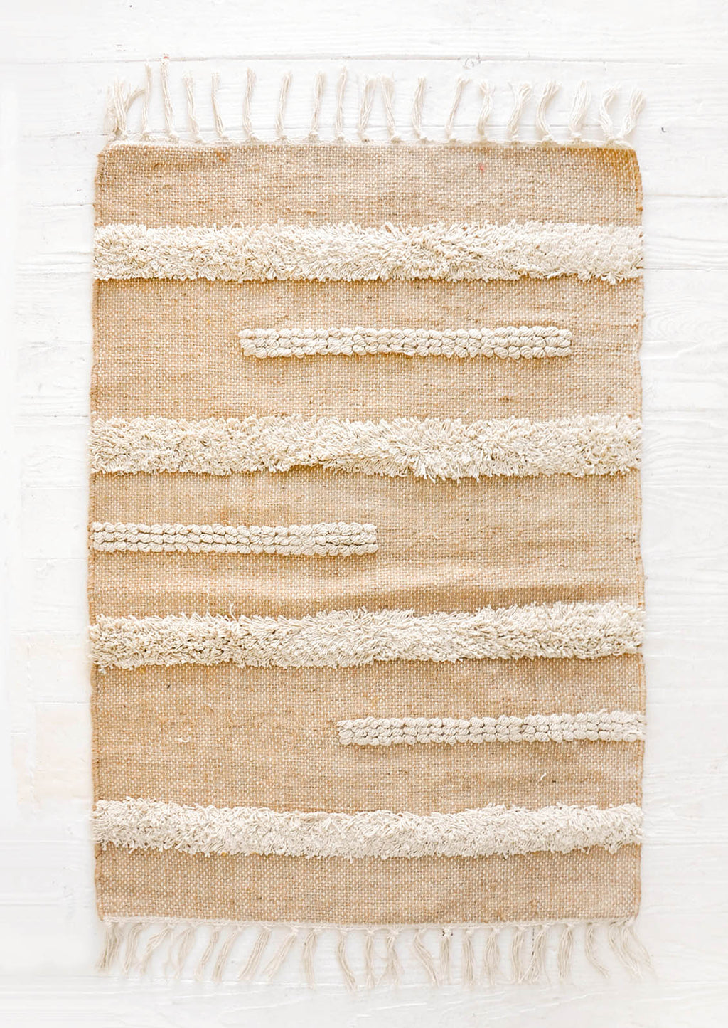 1: Flatweave jute rug in tan with fluffy, raised stripe detailing in ivory, featuring tasseled edges.