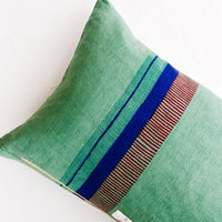 3: Back of linen throw pillow showing a series of block printed stripes and exposed brass zip closure