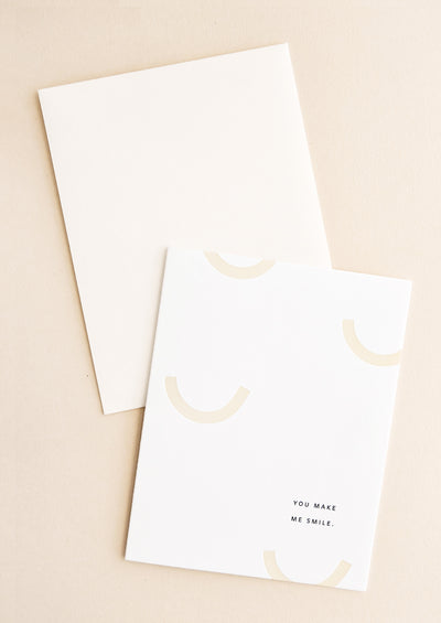 "White greeting card with pastel beige U-shaped arcs, small font at corner reads ""You Make Me Smile""."