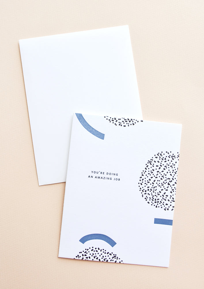 "1: White notecard with black and blue geometric decoration and the text ""You're doing an amazing job"", with white envelope."