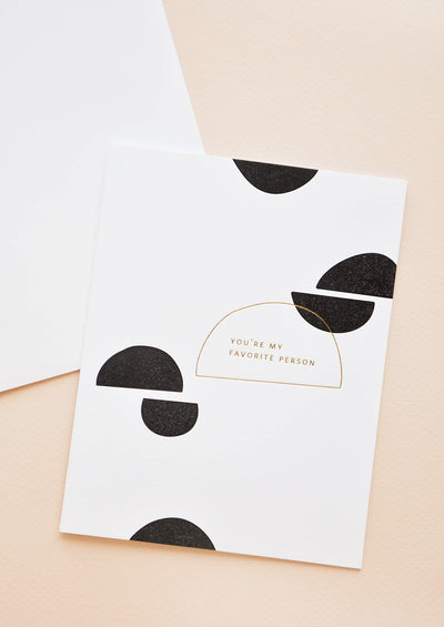 "A white greeting card patterned with a smattering of black semicircular shapes and the words ""you're my favorite person"" in gold foil."