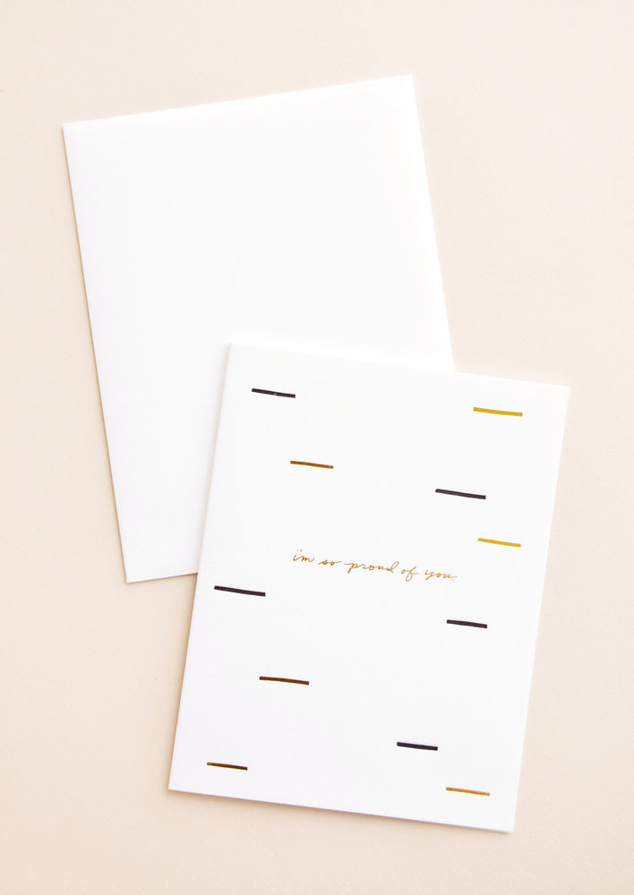 "1: A white envelope and a white greeting card patterned with short lines of black and gold and the words ""i'm so proud of you"" in gold foil."
