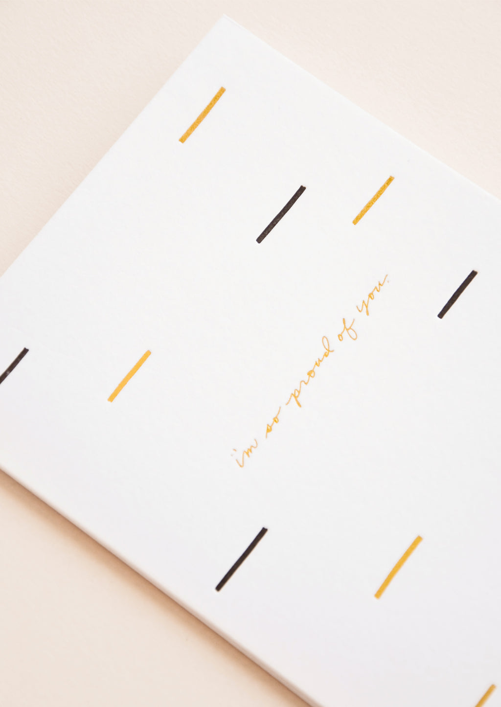 "2: A white greeting card patterned with short lines of black and gold and the words ""i'm so proud of you"" in gold foil."