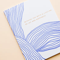 "2: Greeting card with wavy cobalt blue line pattern and gold text reading ""Wishing you both a lifetime of happiness"""