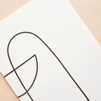 "1: A simple white greeting card with two shapes in black outline and the words ""happy birthday"" in raised text."