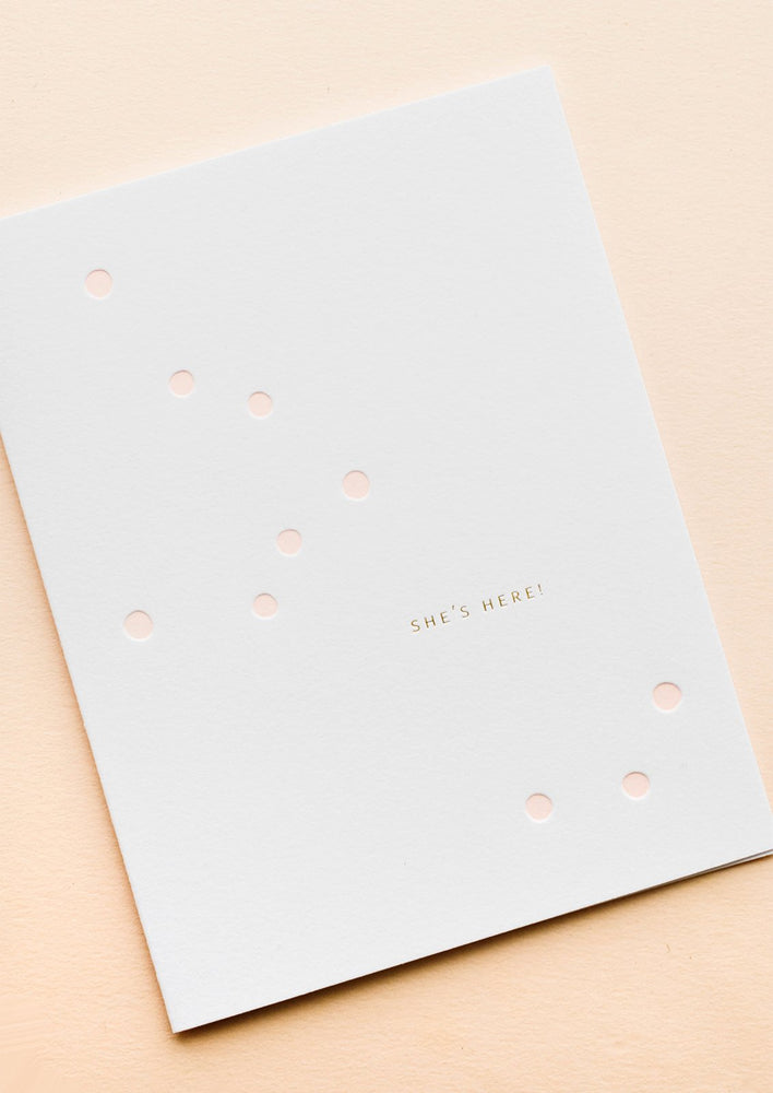 "1: White greeting card with scattered light pink dot and gold text reading ""She's here!"""