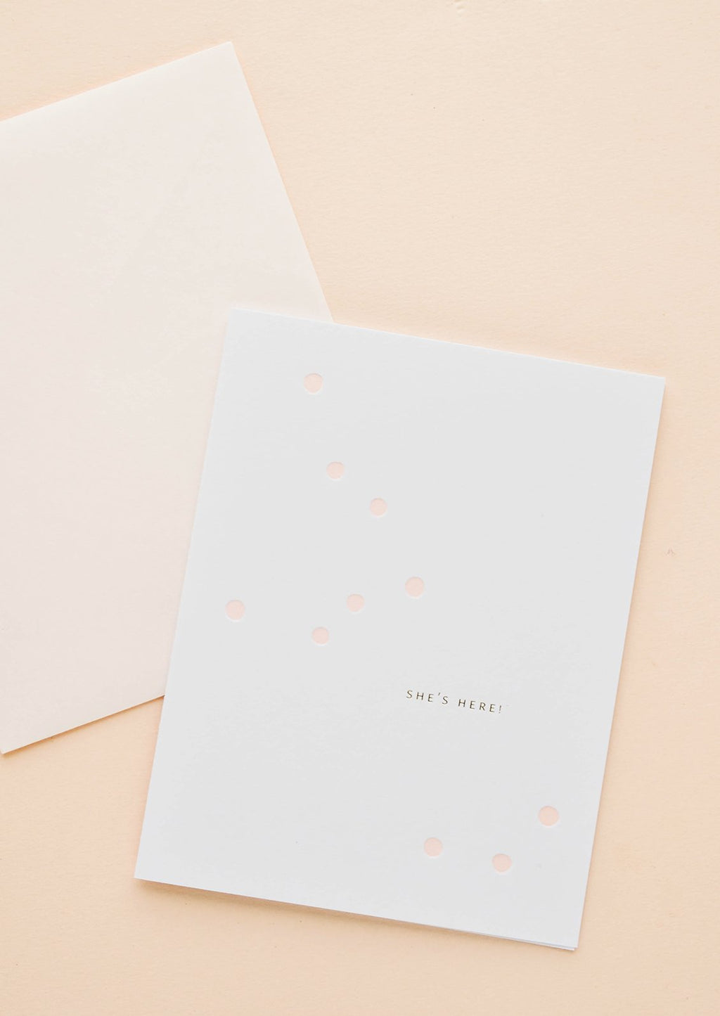 "2: White greeting card with scattered light pink dot and gold text reading ""She's here!"", paired with pale pink envelope"