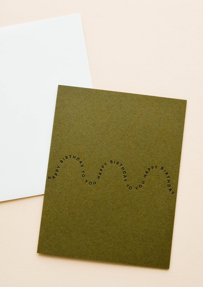 "1: Olive green greeting card with black printed text in a wave-like formation, repeating the words ""Happy birthday"""