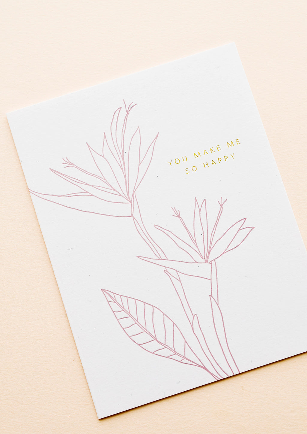 "1: Greeting card with pink flower outline drawing and gold text reading ""You make me so happy"""