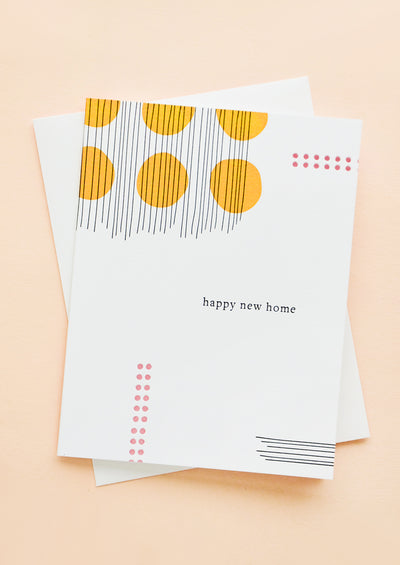 "A greeting card with abstract dot and line print, serif text reads ""happy new home""."