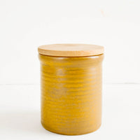 1: Small ceramic jar in rustic, caramel brown glaze with subtle grooves and wooden lid