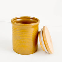 2: Small ceramic jar in rustic, caramel brown glaze with subtle grooves and wooden lid with silicone lining