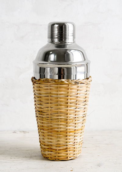 A stainless steel cocktail shaker with rattan cover.
