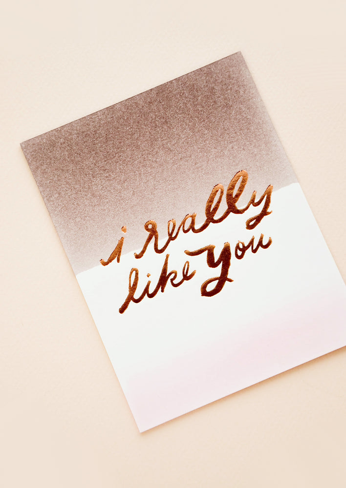 "1: Greeting card with gradient purple to white backgrounds and ""i really like you"" written in gold foil script."