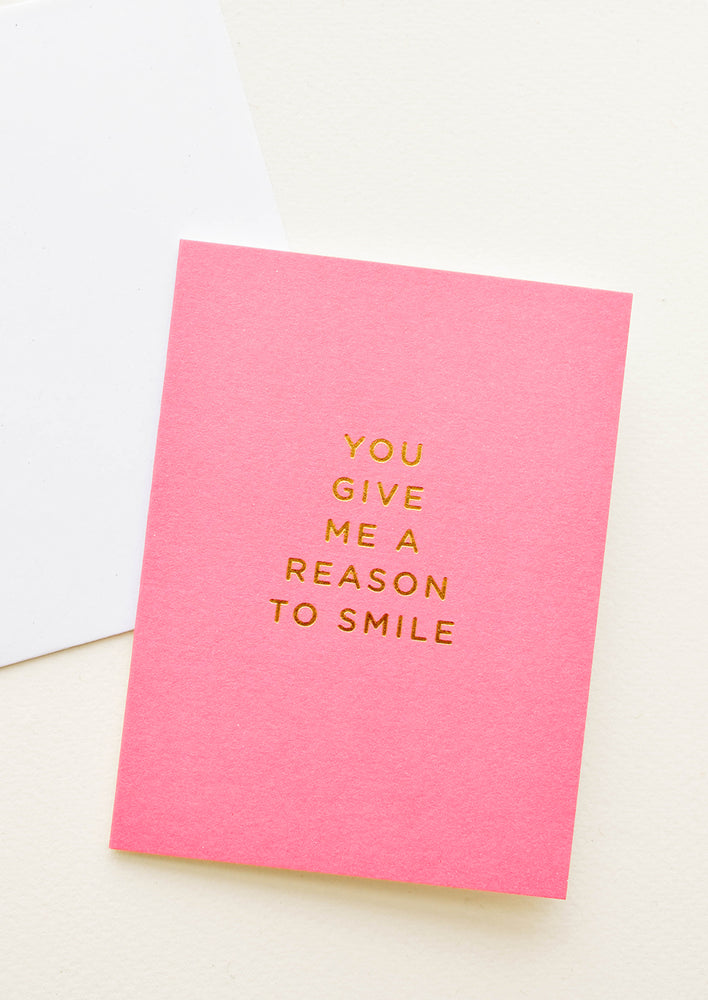 "1: Pink notecard with the text ""You Give Me a Reason To Smile"" in gold foil."