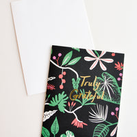 "1: Black greeting card with botanical print and ""Truly Grateful"" written in gold foil. Shown with white envelope."