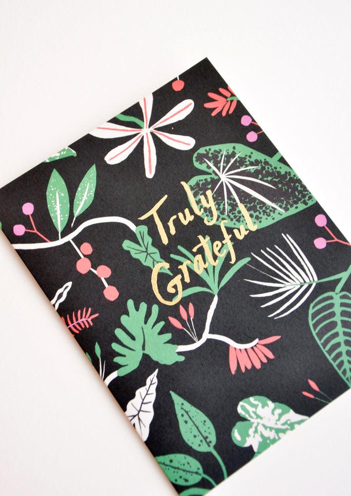 "2: Black greeting card with botanical print and ""Truly Grateful"" written in gold foil."