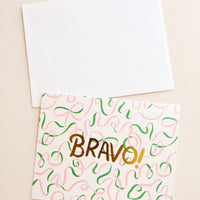"1: A white envelope with a beige card patterned with illustrated green and pink ribbons and the word ""bravo"" in gold foil."