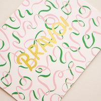 "2: A beige card patterned with illustrated green and pink ribbons and the word ""bravo"" in gold foil."
