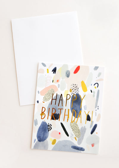 "Notecard with colorful abstract shapes and the text ""Happy Birthday"" in metallic gold, with white envelope"