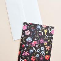 1: Notecard with colorful floral decoration on black background, and the text Congratulations in metallic pink script, with white envelope.