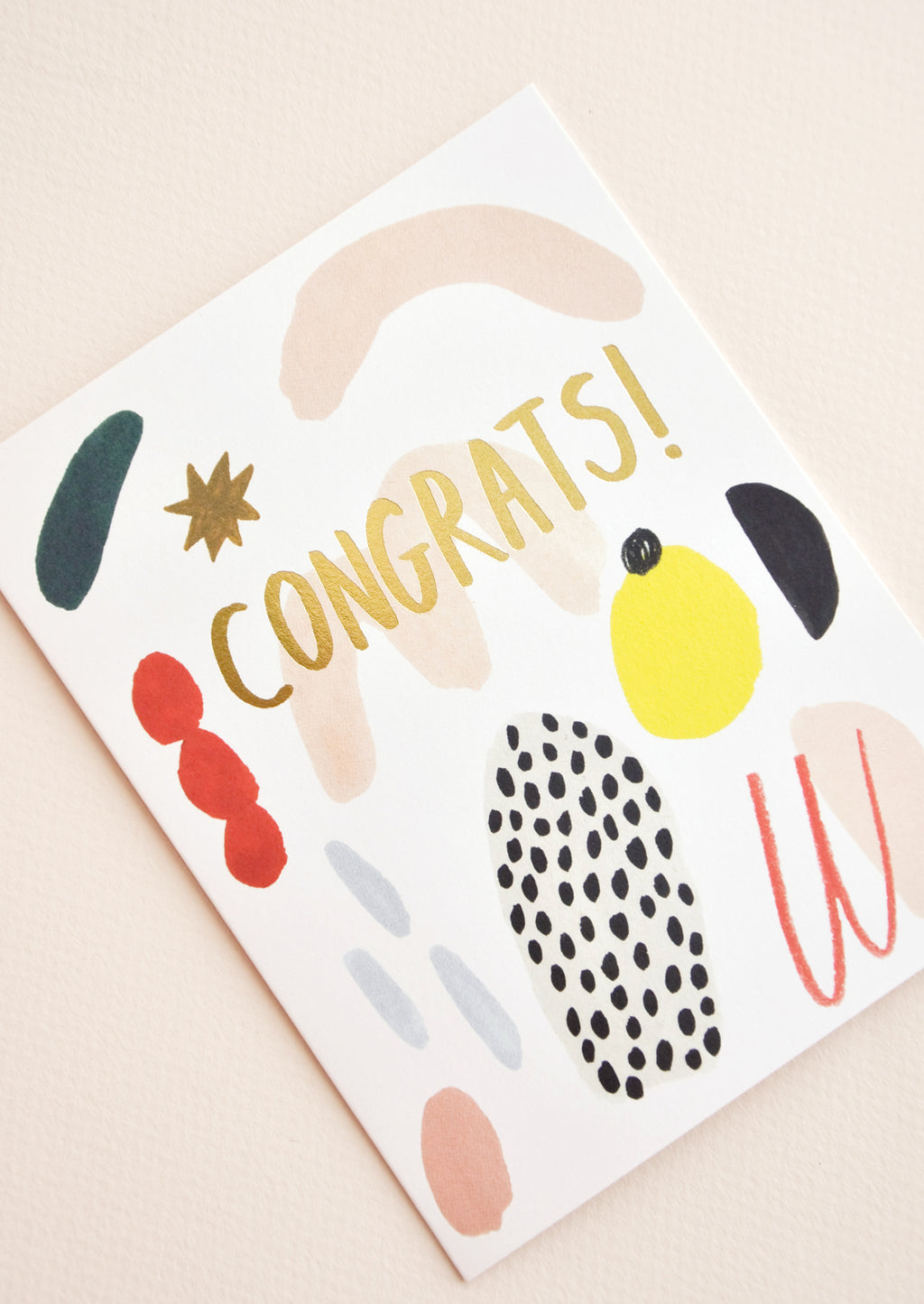 "2: Close up of notecard with colorful abstract shapes and the word ""Congrats"" in gold."