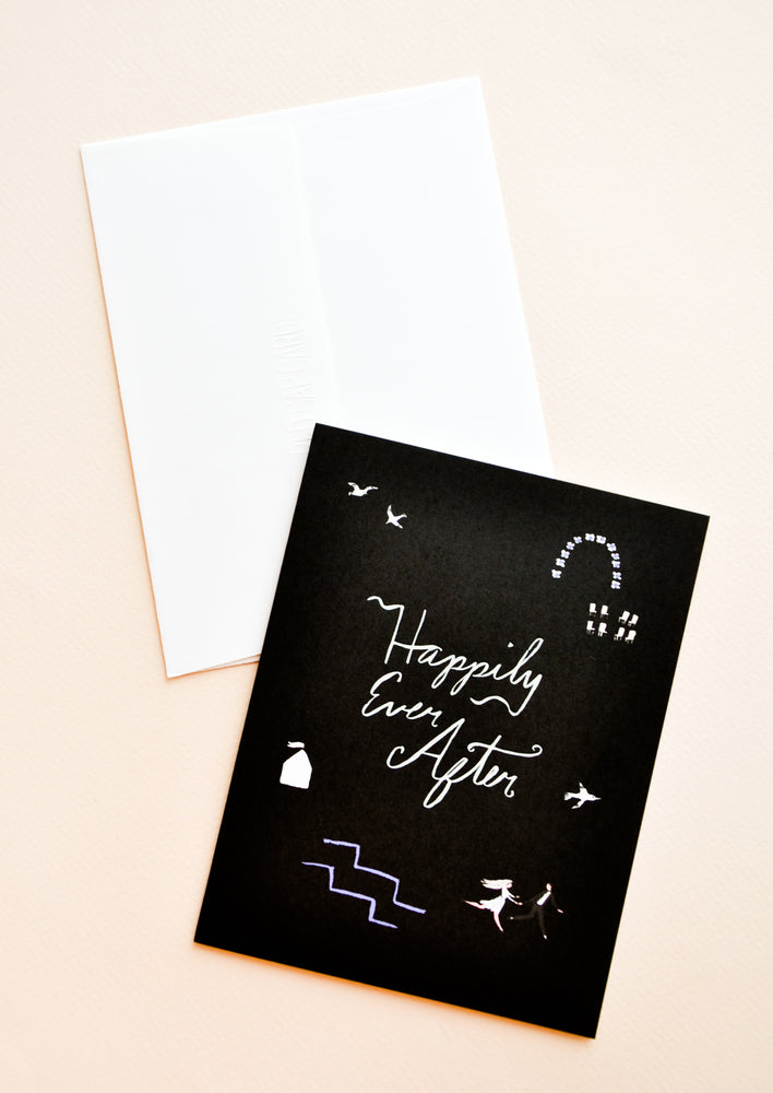"Black notecard with white abstract decoration and the text ""Happily Ever After"" with white envelope."