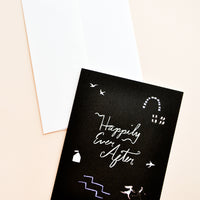 "1: Black notecard with white abstract decoration and the text ""Happily Ever After"" with white envelope."