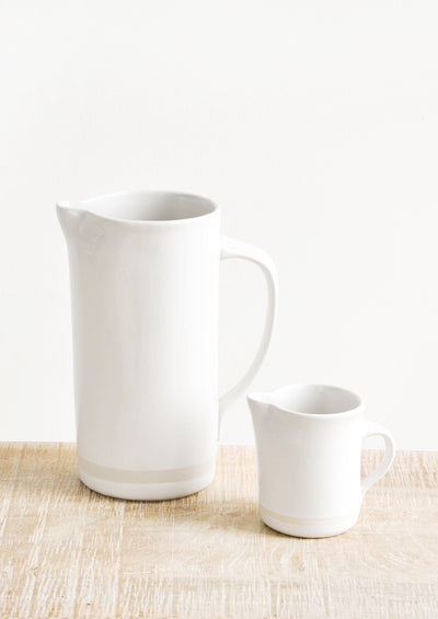 A large white ceramic pitcher next to a small white ceramic creamer.