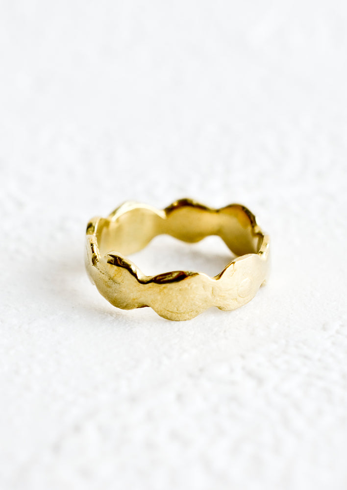 1: A brass ring in an organic, curvy shape.