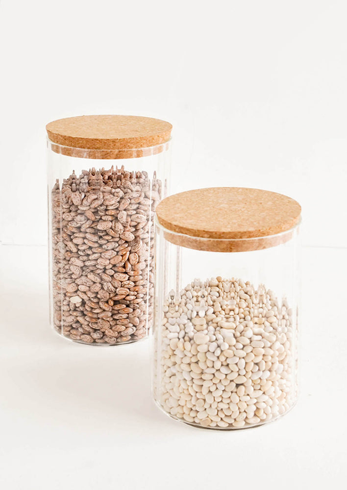 1: Two horizontally ribbed glass jars filled with beans and lidded with cork.