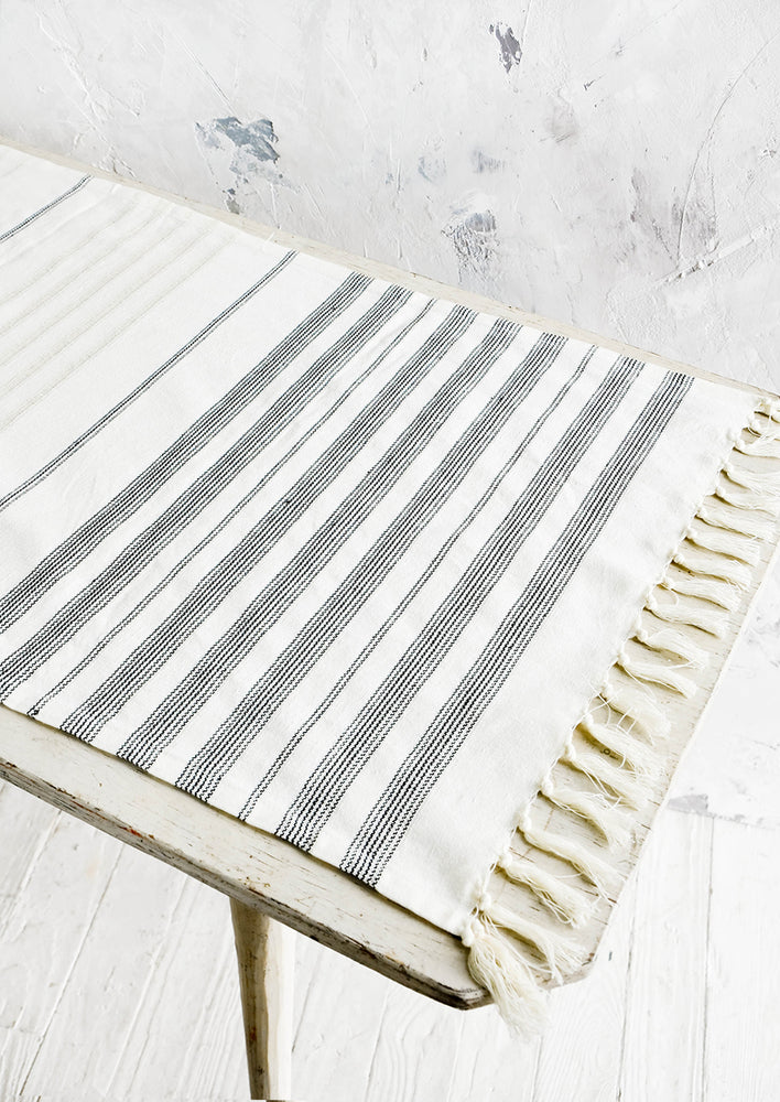 2: Ivory and black striped woven cotton table runner displayed on a table