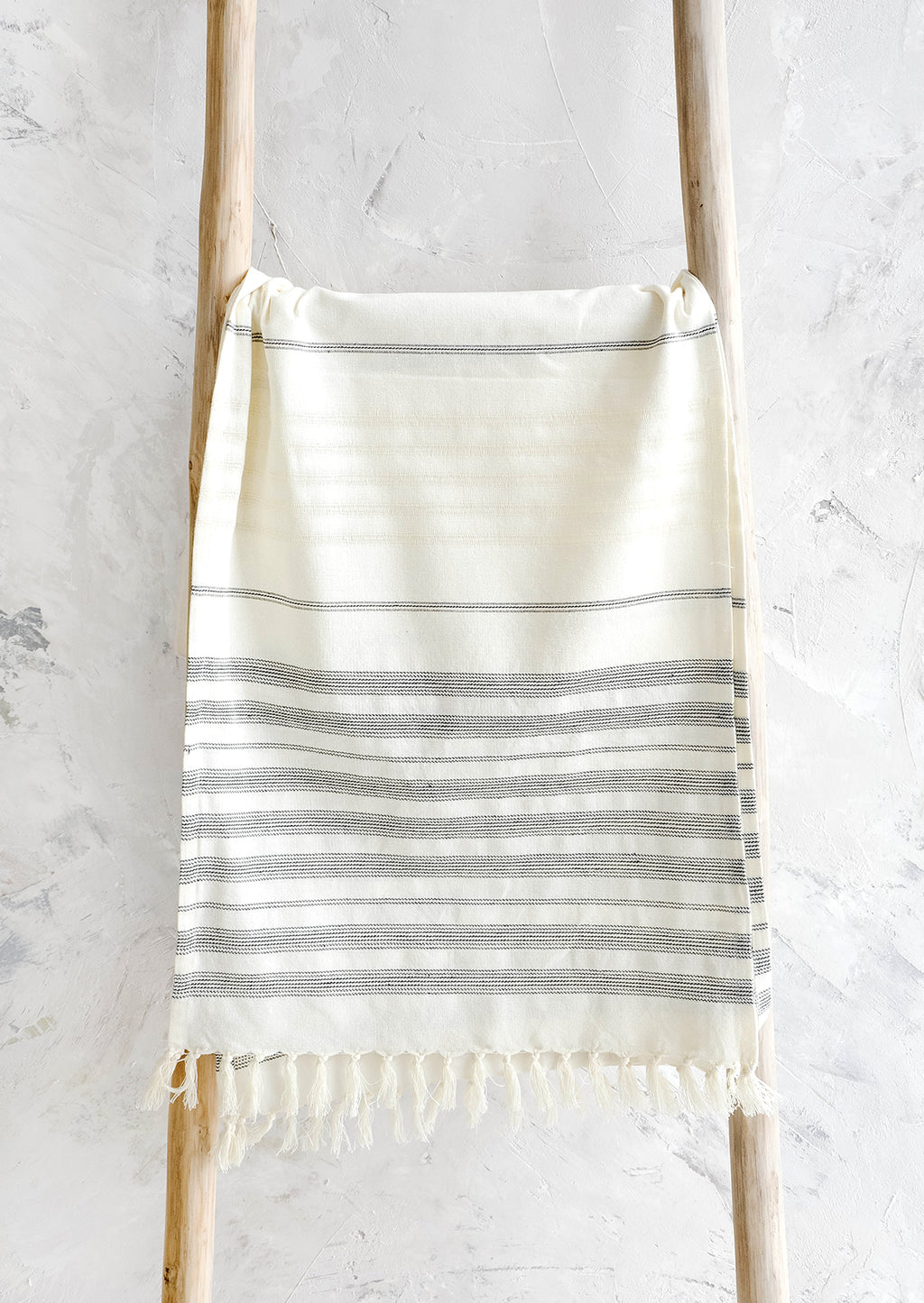 1: Ivory and black striped woven cotton table runner hanging on a wooden ladder
