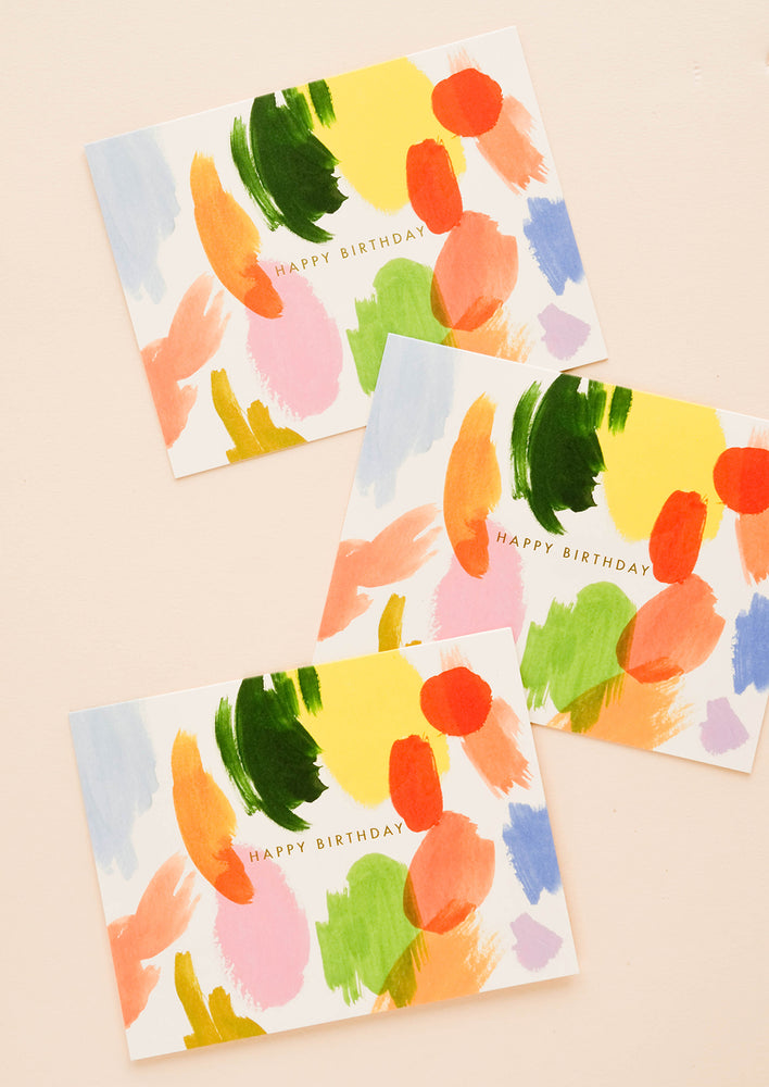 "1: Multiple cards in the same design, showing multicolor paint strokes and ""Happy Birthday"" text in golden letters"
