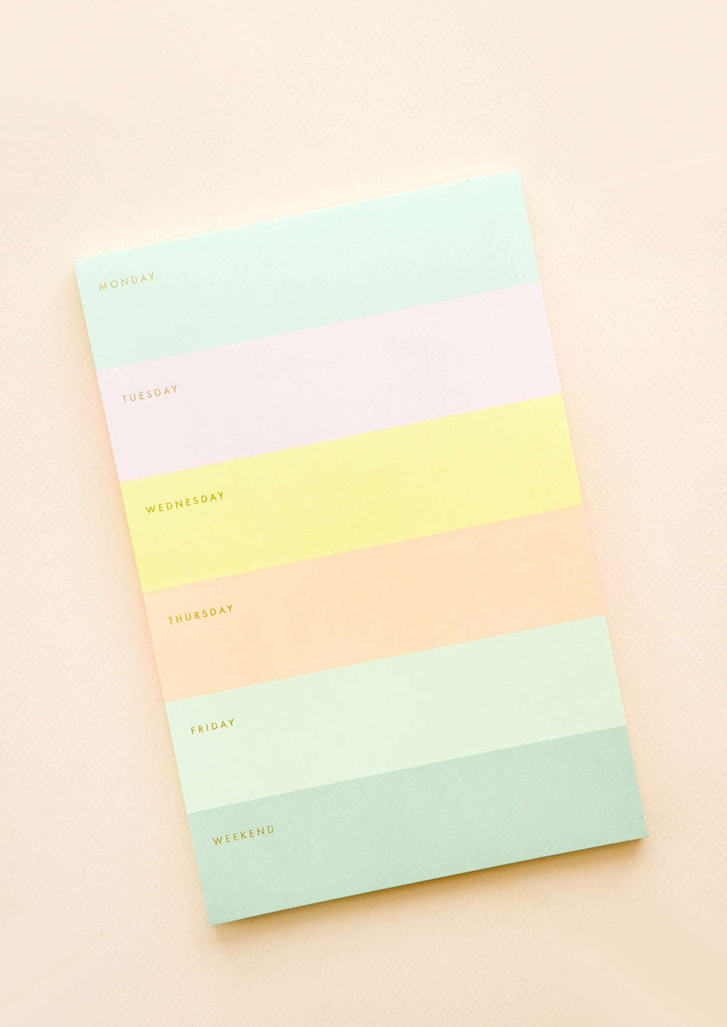 1: Color blocked weekly planner desktop notepad with each day corresponding to a different color.