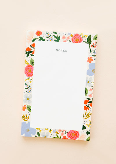 Small notepad decorated with a border of drawings of roses and blank paper.