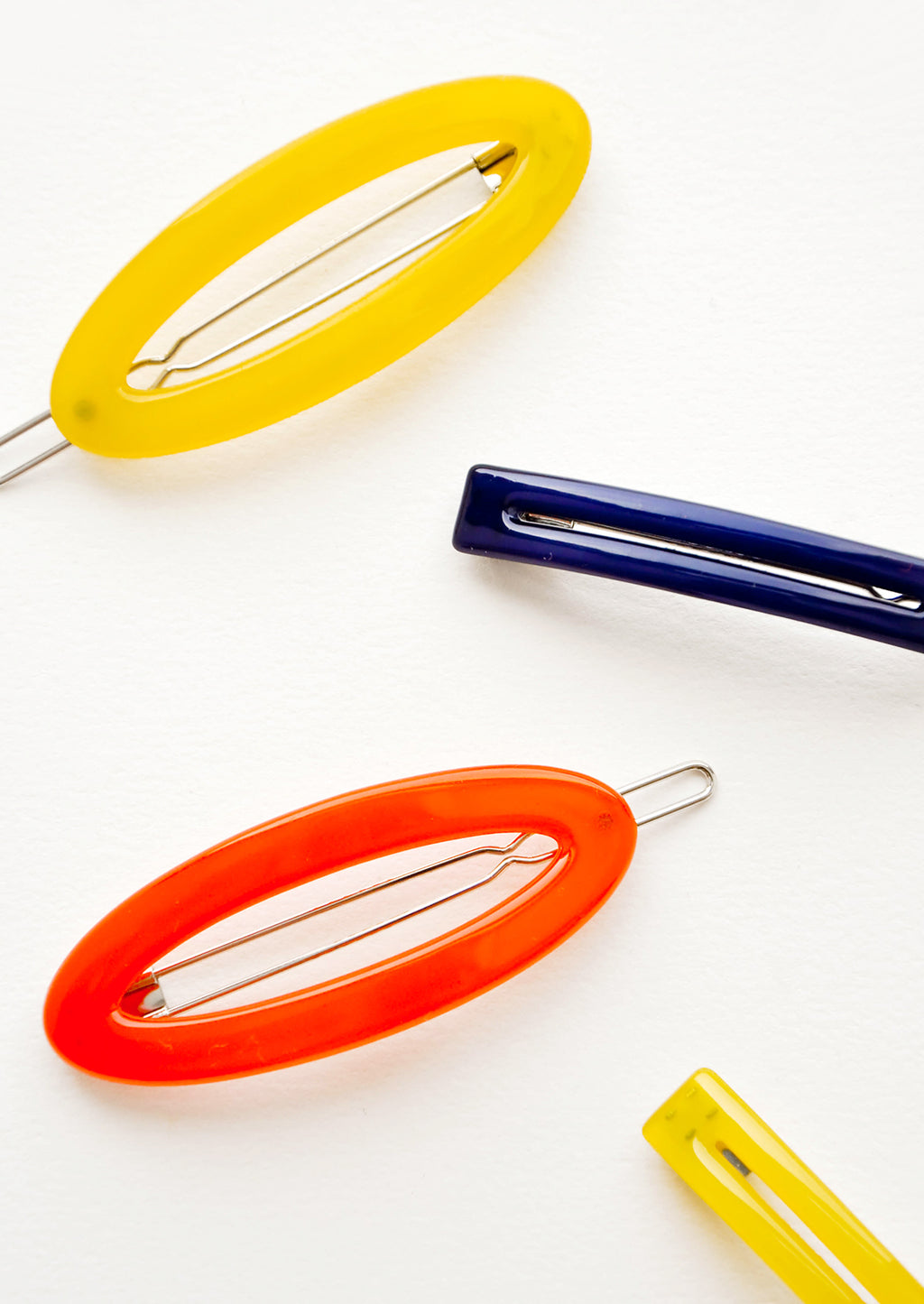 1: Four hair clips in yellow orange and blue